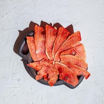 Suprimentos de inverno: fatias de melancia seca em placa de madeira em fundo branco com sombra profunda.