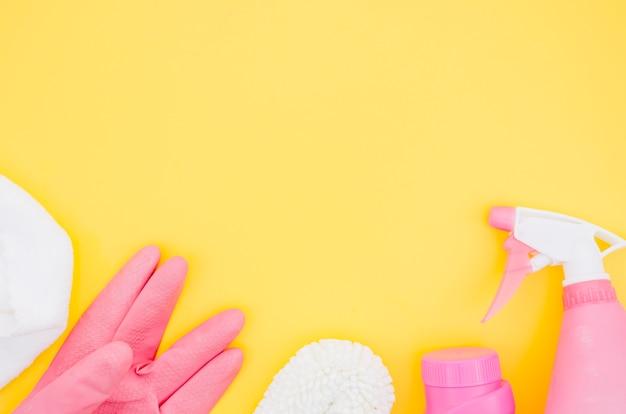 Suprimentos de limpeza-de-rosa e branco em pano de fundo amarelo