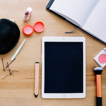 Suprimentos de maquiagem perto de tablet e notebook