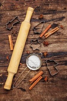 Suprimentos de panificação de natal, utensílios de cozinha, temperos, cortadores de biscoitos - estrelas, anjo e abeto, peneira, açúcar em pó e um rolo. tábuas de madeira velhas