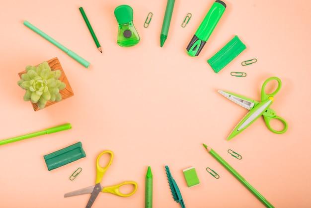 Suprimentos de papelaria e planta em vaso, formando uma moldura circular sobre a superfície colorida