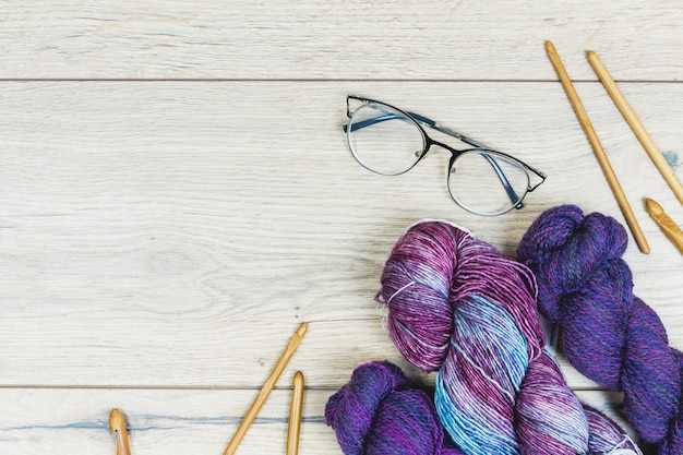 Suprimentos de tricô e óculos na mesa de madeira