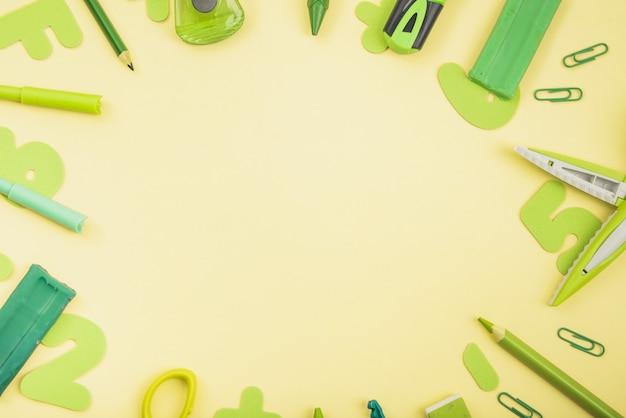 Suprimentos escolares de cor verde dispostos em forma circular sobre fundo amarelo