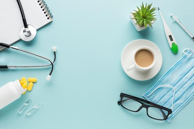 Suprimentos médicos com xícara de café e planta suculenta em pano de fundo azul