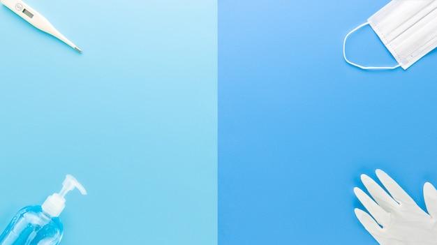 Suprimentos médicos para permanecer seguro e proteger do coronavírus nos cantos da vista superior azul com espaço para texto