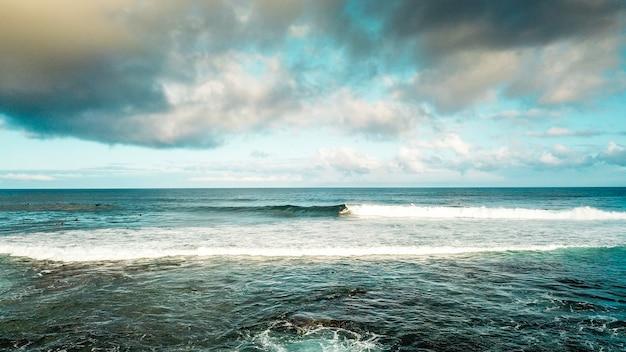 Surf break spot no oceano em ront of the beach. férias e atividade esportiva de surfe com muitas pessoas nadando nas ondas. divirta-se e curta a natureza com mesas de surf