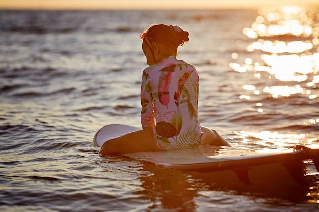 Surf e férias. férias na praia. menina relaxada sentada na água com prancha, apreciando o pôr do sol