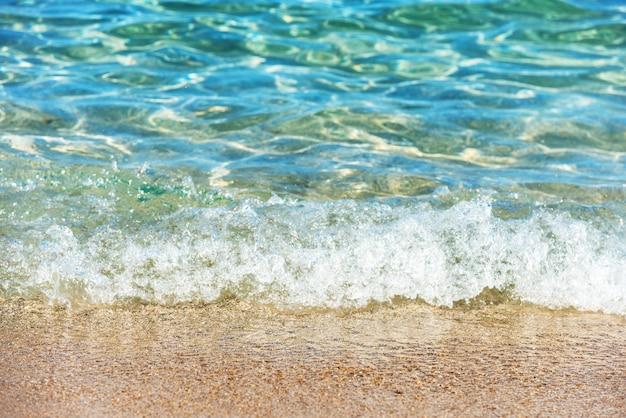 Surf na praia. areia quente e água do mar límpida e azul no fundo