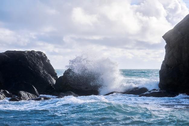 Surf tempestuoso com respingos entre as rochas costeiras na costa do mar de inverno