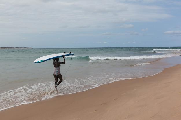 Surfista africana caminhando com uma prancha de surfe até o oceano