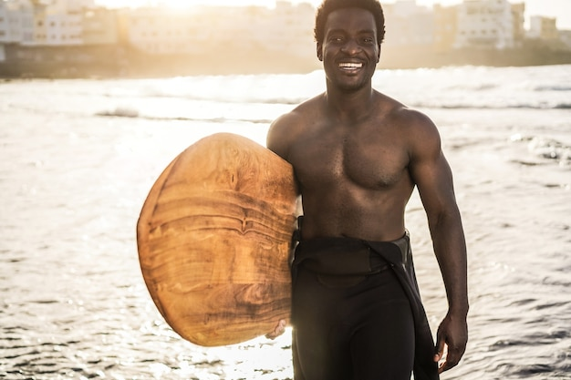 Surfista africano segurando uma prancha de surf vintage na praia ao pôr do sol - foco no rosto