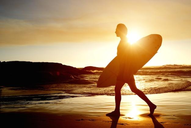 Surfista, andar praia, com, surfboard, durante, pôr do sol