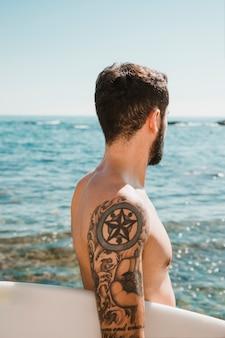 Surfista anônima olhando acenando do mar