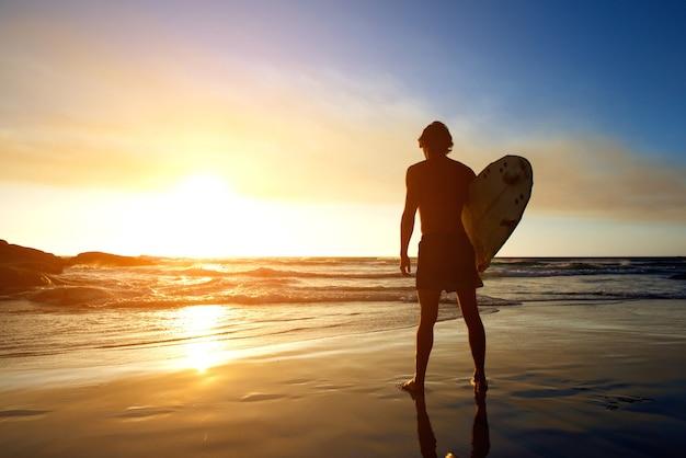 Surfista assistindo o pôr do sol na praia