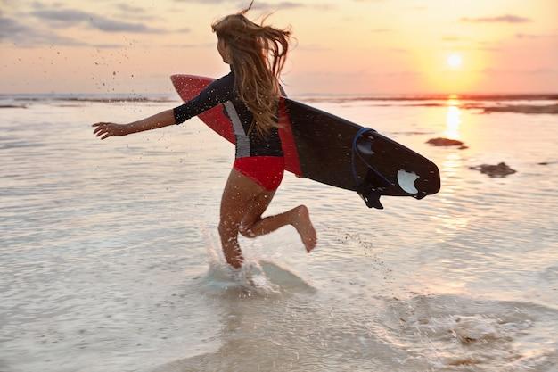 Surfista ativo corre para o oceano com felicidade, faz respingos de água, carrega bodyboard debaixo do braço