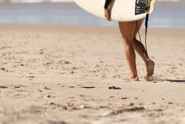 Surfista australiana caminhando pela praia com sua prancha de surf. noosa, queensland, australia.lis