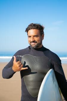 Surfista barbudo alegre em pé com uma prancha de surf e sorrindo