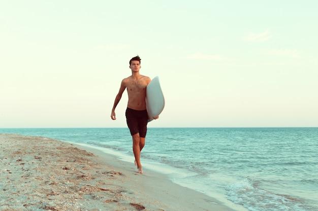 Surfista bonita segurando sua prancha de surf