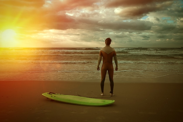 Surfista com prancha na praia observando as ondas ao pôr do sol