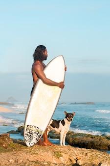 Surfista com um cachorro pelo oceano