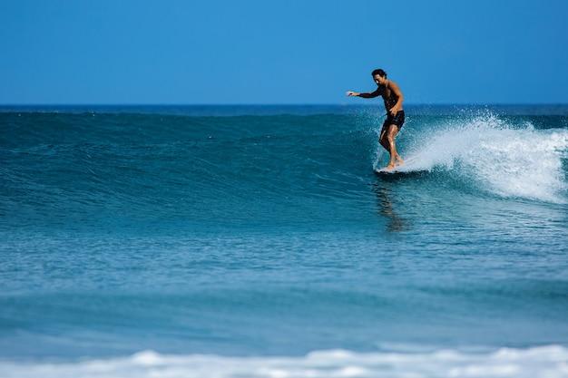 Surfista coreano cavalga um longboard nas ondas azuis