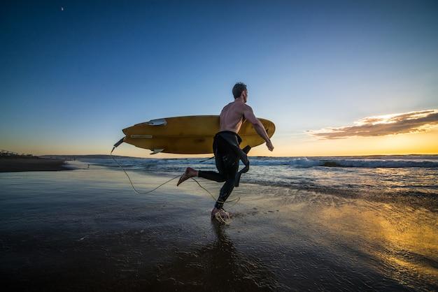 Surfista correndo na água com prancha de surf ao pôr do sol