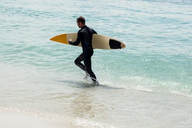 Surfista correndo na praia com uma prancha de surf