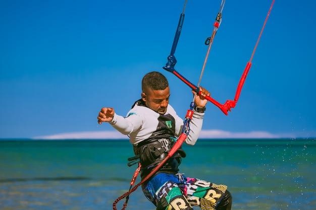 Surfista de close-up, segurando a corda de pipa. mar vermelho.