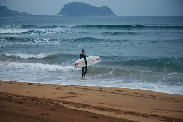 Surfista de meia-idade com roupa de neoprene caminhando na água em uma praia arenosa entre colinas