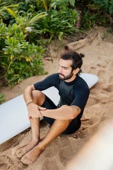 Surfista e sua prancha de surf sentados na areia
