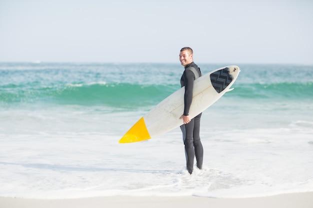 Surfista em pé na praia com uma prancha de surf