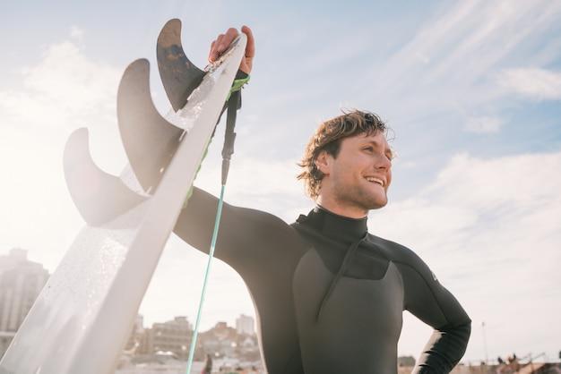 Surfista em pé na praia com uma prancha de surf.