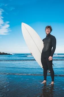 Surfista em pé no oceano com sua prancha de surf.