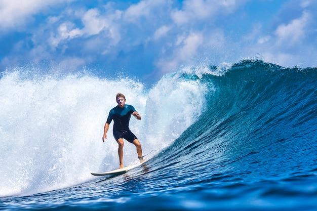 Surfista em uma onda azul em um dia ensolarado