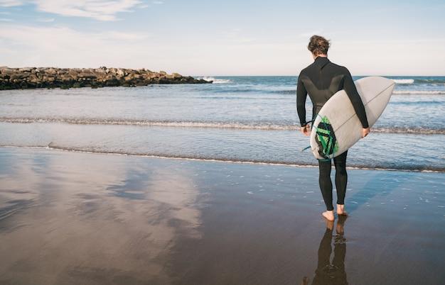 Surfista entrando na água com sua prancha de surf.