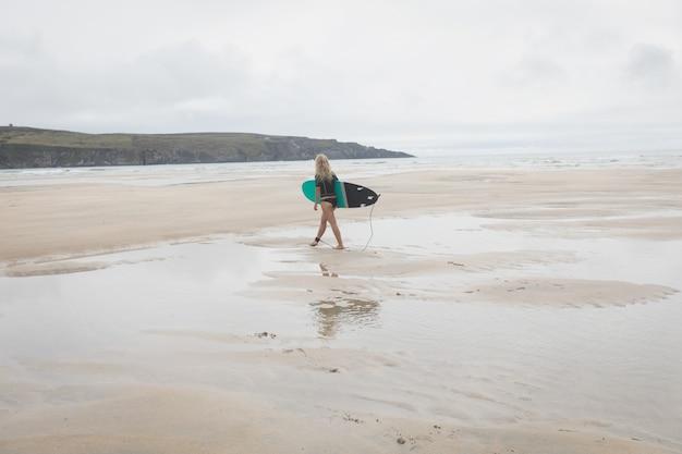 Surfista feminina andando na praia com prancha de surf