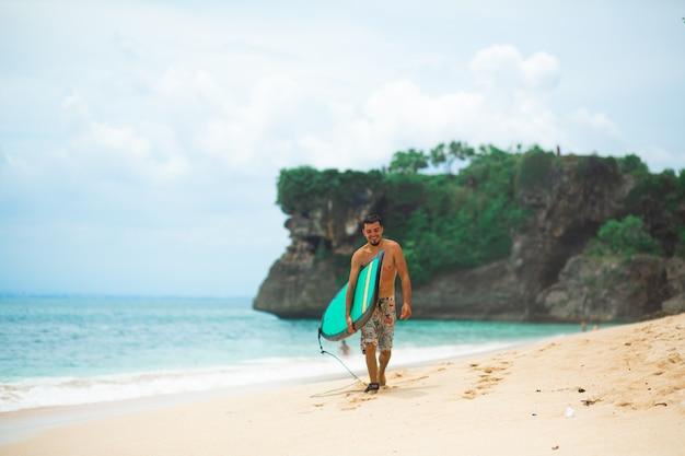 Surfista. homem de surf com prancha de surf, caminhando na praia tropical. estilo de vida saudável, atividades aquáticas, esportes aquáticos. lindo oceano