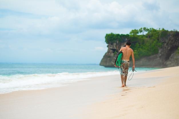 Surfista. homem de surf com prancha de surf, caminhando na praia tropical.