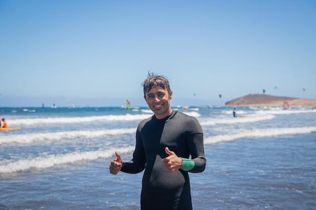 Surfista indiano atraente na praia está feliz e relaxado mostrando os polegares para cima, o dia é fantástico