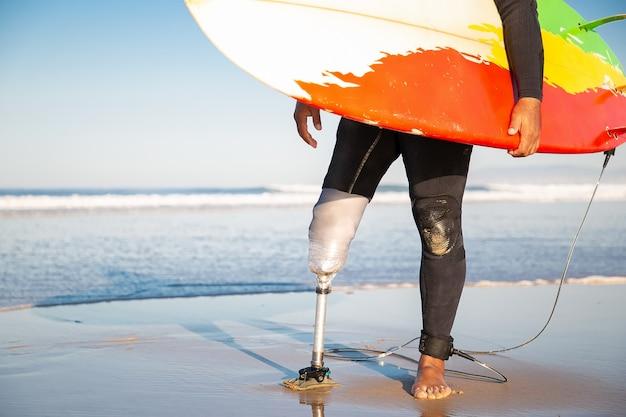 Surfista irreconhecível em pé com uma prancha de surf na praia