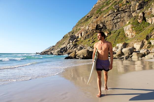 Surfista masculina atraente, caminhando na praia com prancha de surf