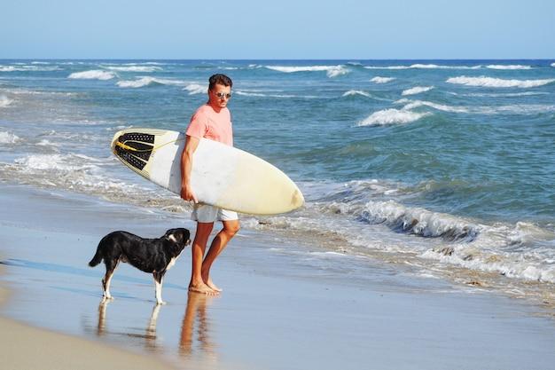 Surfista masculina na praia com um cachorro.