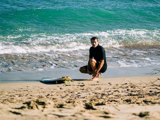 Surfista masculino amarrando a trela da prancha na perna na praia. oceano atlântico.