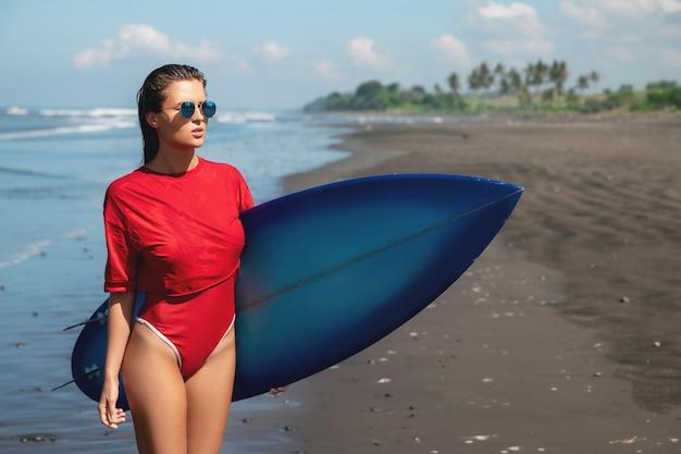 Surfista mulher com shortboard na praia
