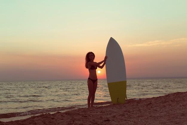 Surfista na praia ao pôr do sol