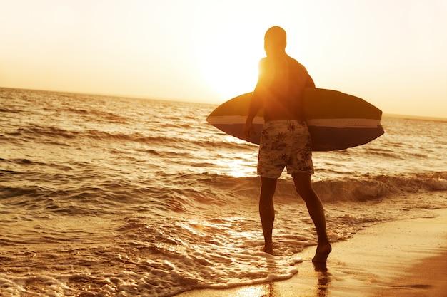 Surfista na praia do oceano ao pôr do sol