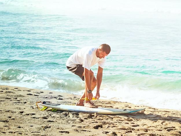Surfista pega uma coleira de surf. praia pelo oceano atlântico.