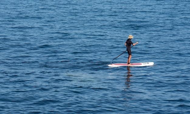 Surfista remando em sua prancha
