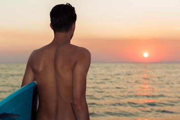 Surfista segurando sua prancha de surf e à procura de ondas