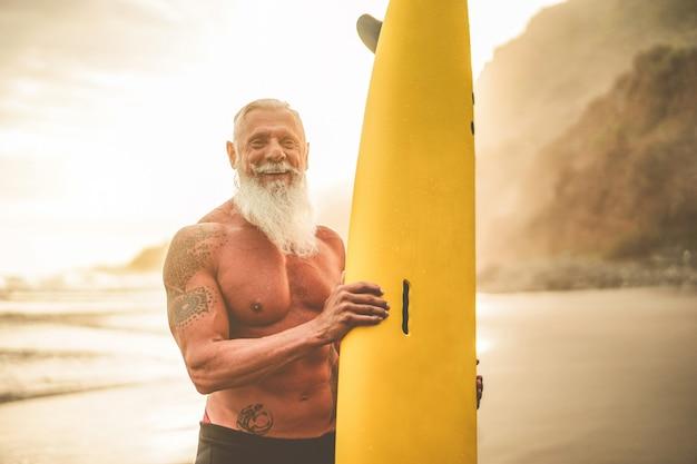 Surfista sênior tatuado segurando a prancha de surf na praia ao pôr do sol - velhote feliz se divertindo fazendo esportes radicais - alegre conceito idoso - foco em seu rosto